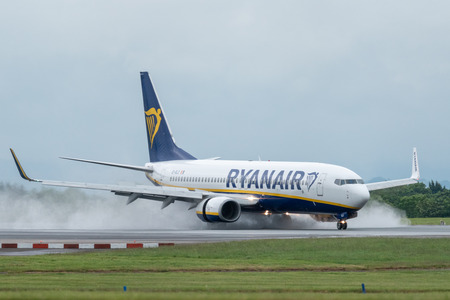 MANCHESTER UK, 30 MAY 2019: Ryanair Boeing 737 flight FR3217 from Milan lands on runway 23R at Manchaester Airport. Reverse engine thrust kicks up rain as spray from the tarmac.