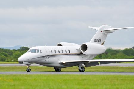 MANCHESTER UK, 30 MAY 2019: An AirX Cessna 750 Citation X executive jet turns off runway 23R at Manchaester Airport after landing.