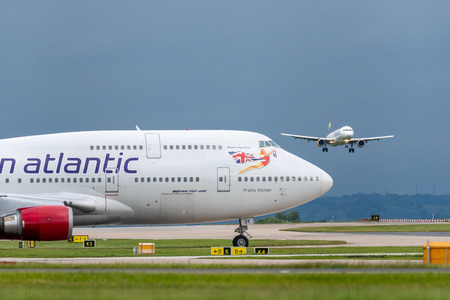 MANCHESTER UK, 30 MAY 2019: Virgin Atlantic Boeing 747 Pretty Woman waits  on the apron for Thomas Cook Airlines flight MT1747 to land before taxiing to take off
