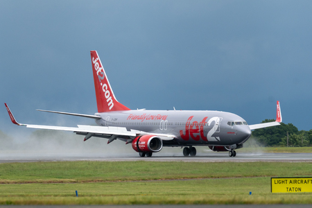 MANCHESTER UK, 30 MAY 2019: Jet2 Boeing 737 flight LS804 from Barcelona lands on runway 23R at Manchaester Airport with rainwater spraying up from the engines reverse thurst.