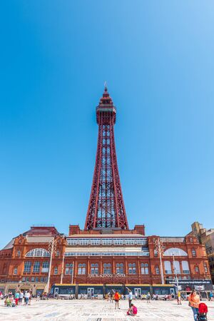 BLACKPOOL, UK, JUNE 30 2019: Tourists gather and relax in front of Blackpool Tower on the Comedy Carpet as an electric tram passes by.