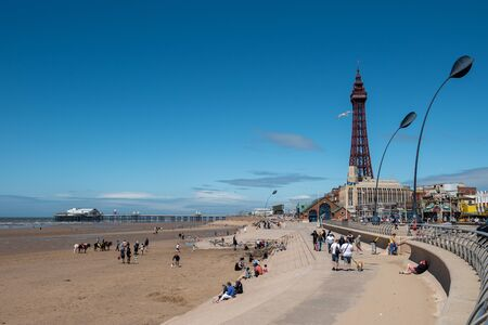 BLACKPOOL, UK, JUNE 30 2019: A photograph documenting the view looking North along the seafront towards Blackpool Tower from Central Pier.