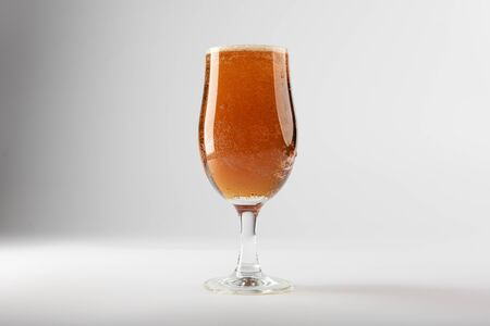 A full beer glass containing golden ale set against a clean background.