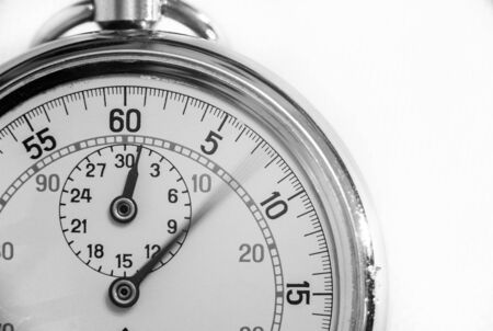 A black and white close up macro view of a pocket watch. Long exposure blurred the second hand giving an impression of passage of time.