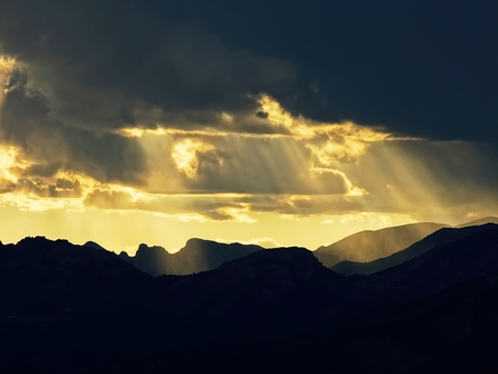 Sunbeams through the clouds on mountain photo