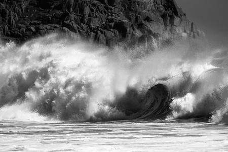 黒と白のビーチでクラッシュするいくつかの波のビューを閉じる