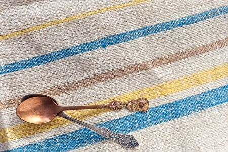 Two vintage spoons on linen fabric