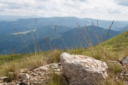 landsape: Montain landsape with a rock and grasses in foeground in the summer