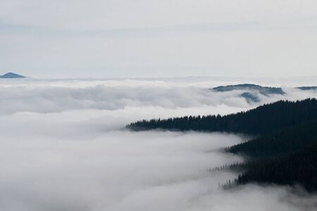 Mountain landscape of the ridge covered by clouds