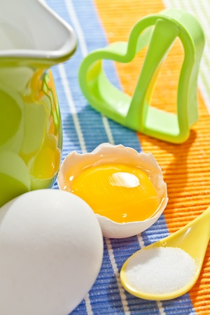 Cookies making: fresh eggs, green jug, milk, salt and cookie form photo