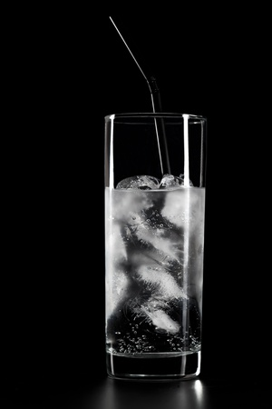 Glass of water and ice on black background