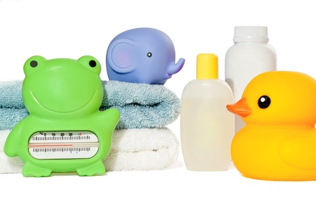 Baby bath accessories isolated: towels, toys, thermometer and bottles with copy space photo