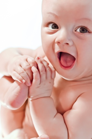 Happy baby playing with hands and legs on white background photo