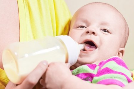 Little smiling baby and bottle on the hands of his mother