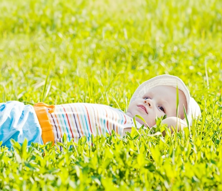 Little dreaming baby laying on the grass