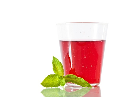 Berry compote with fresh mint leaf in glass isolated