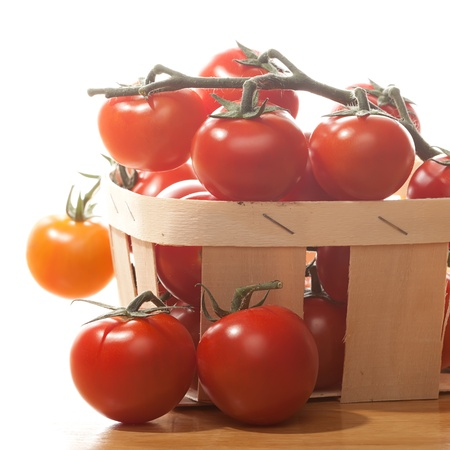 Tomatoes in basket isolated on white background photo