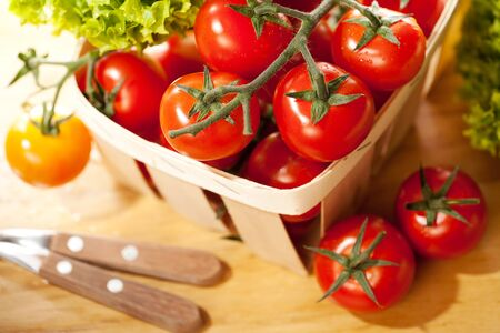 Tomatoes and salad in basket on wooden table photo