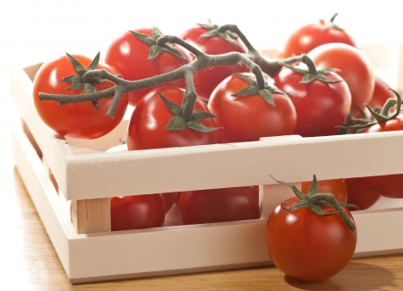 Tomatoes in basket isolated on white background