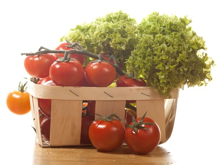 Tomatoes and salad in  wooden basket on the table isolated photo