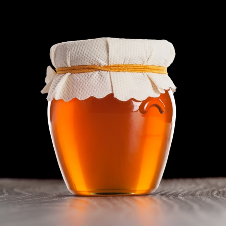 Glass jar with honey isolated on black background Stock Photo