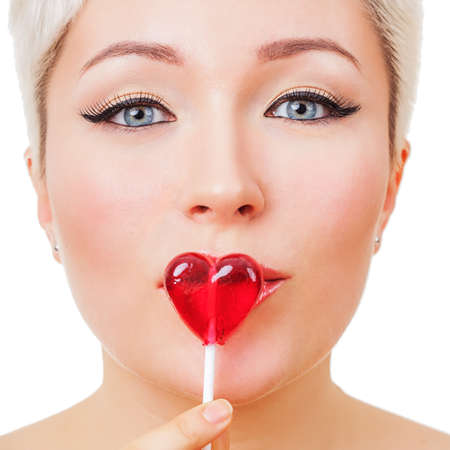 Face portrait of beautiful young woman with heart lollipop photo