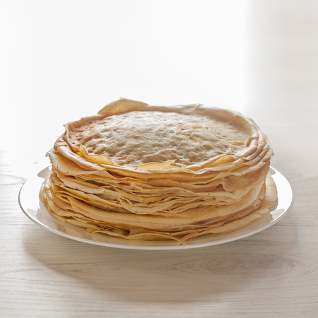 Stack of pancakes on white table