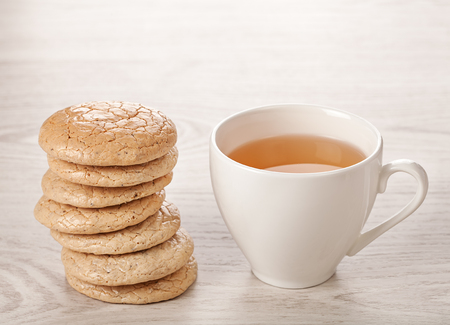 Hot tea in white cup with cookies