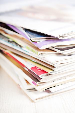 Stack of paper magazines on white table