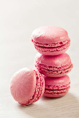 Pink macaroons french sweets stack on light background