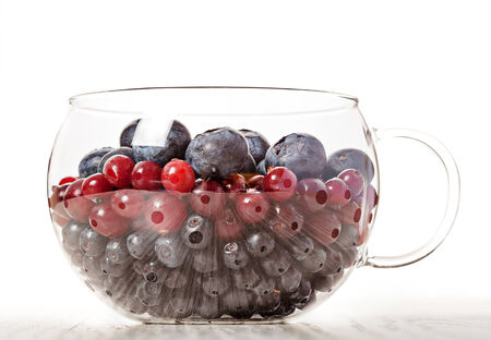 Berries assortment blueberry, cranberry and bilberry in glass bowl