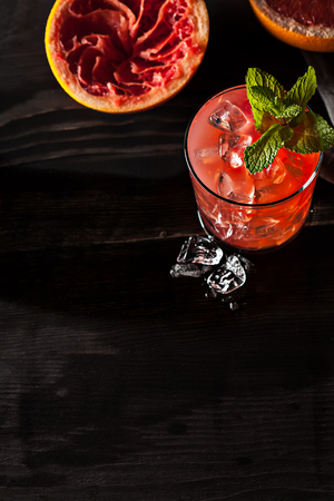 Juicy cold grapefruit drink on dark table