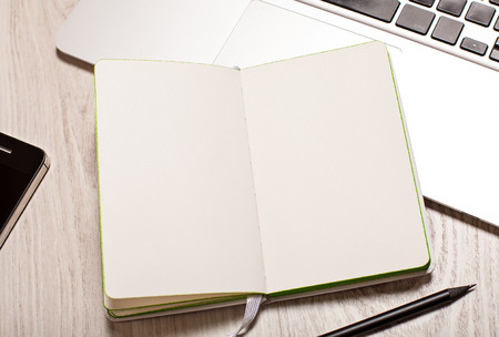 Open paper notepad with blank pages on white table with laptop