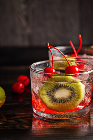Cold summer cocktail drink with red cherry and kiwi Stock Photo