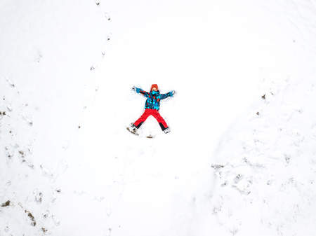 Winter aerial drone landscape with fun kid on snow