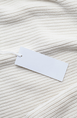 Clothes label tag on cloth background blank white branding template mockup Stock Photo