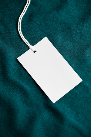 Clothes label tag on dark color cloth background blank white branding template mockup Stock Photo