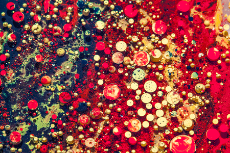 Oil and ink bubbles red and golden colorful abstract drops macro background