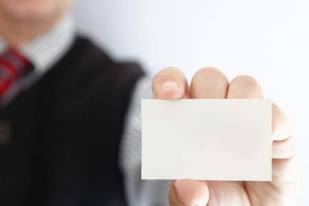 Businessman showing business card - focus on fingers and card. You can just add your text there.  photo