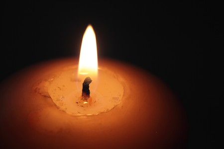 closeup of a burning candle against dark background  Stock Photo