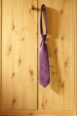red Striped Necktie hung from a hook wardrobe