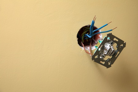 electrician installing a power socket wall background, Dirty socket hanging out of the wall  photo