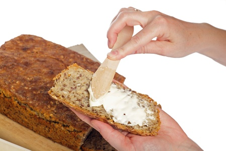 hand bread slices on a board with a knife - white background photo