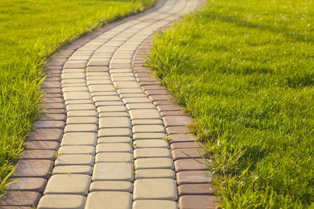 pavers: Garden stone path with grass growing up between and around stones, Brick Sidewalk  Stock Photo