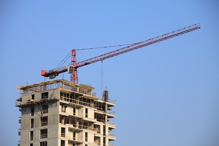 Construction works on a highrise building with cranes over a blue sky
