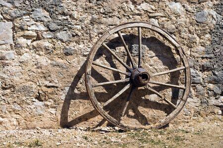 antik: wheel at a brickwall wagon stone wall.    Stock Photo