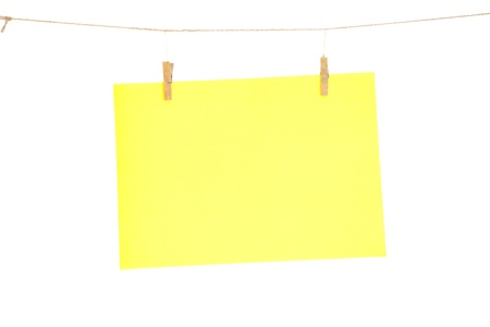 Yellow blank paper sheet on a clothes line. Isolated on white background.  photo