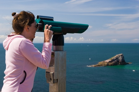 Woman to look through binoculars - sea and blue sky photo
