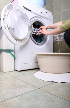 woman loading Preparation washing machine in bathroom clothes in the washing machine photo