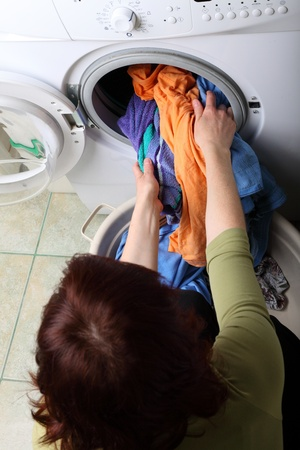 washing clothes: woman loading Preparation washing machine in bathroom clothes in the washing machine Stock Photo